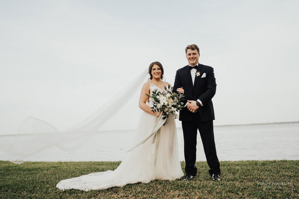 bride in white wedding dress with large bouqet of flowers and vail flowing in the wind on the left. Groom on the right in suit with hands clasped. Both people are smiling.