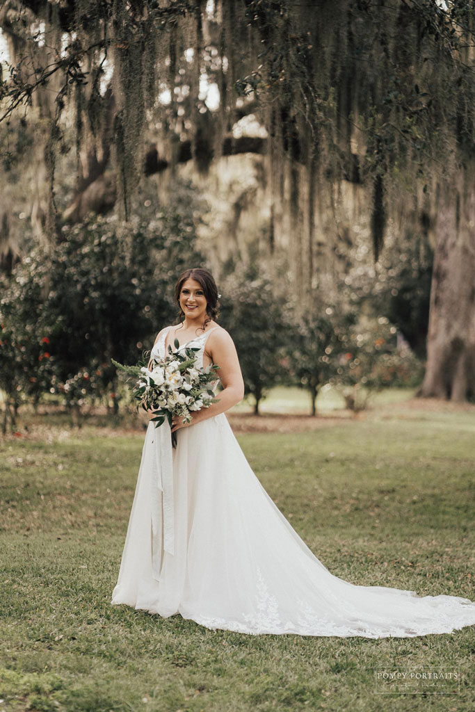 Smiling bride in white wedding dress holding bouqet of flowers under moss strewn trees