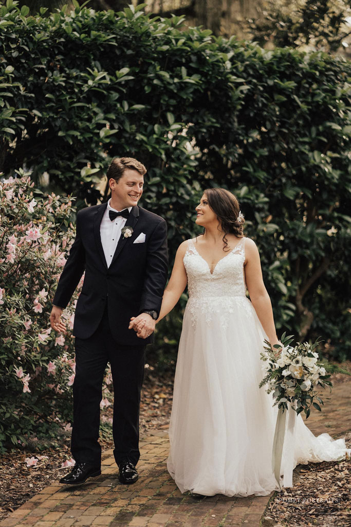 Groom in a suit, left, walkning hand and hand with bride, on right. Both looking in to each other's eyes and smiling
