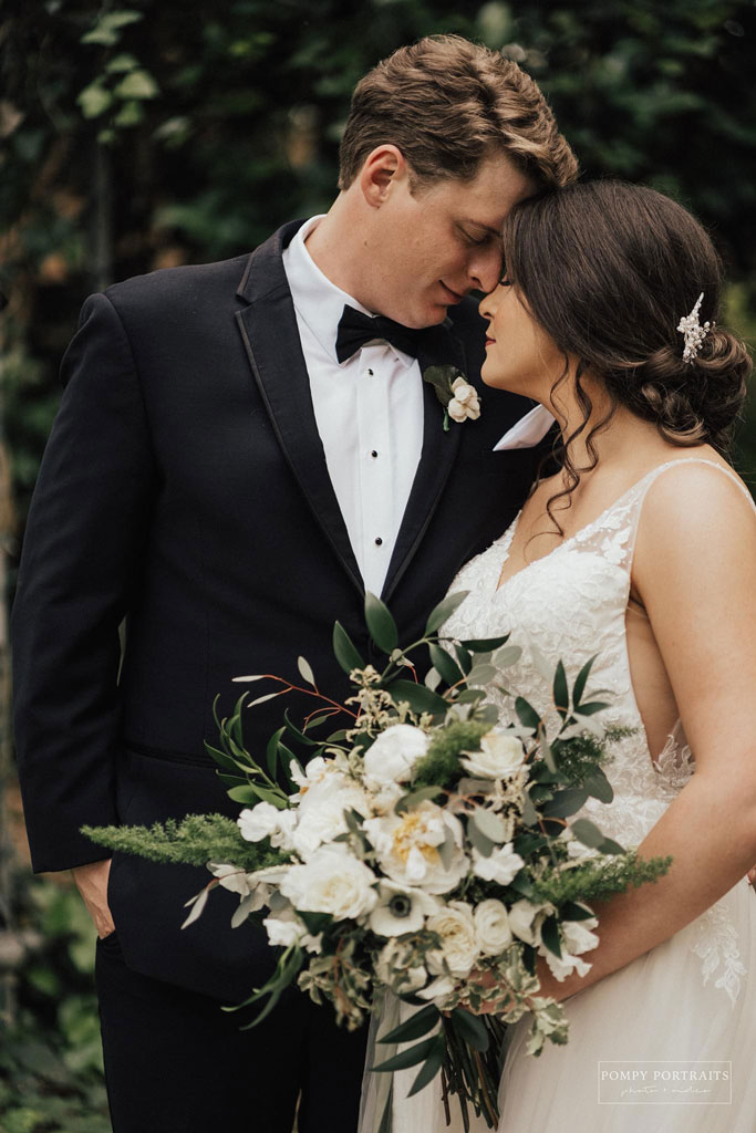 Groom, in dark suit on left, nuzzling against Bride, on the right, wearing a white wedding dress and holding a bouqet of flowers.