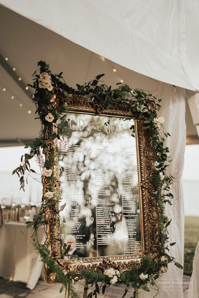 Mirror framed with flowers and flora with writing on the mirror. Headline reads 'Find your seat' with columns of guest names below