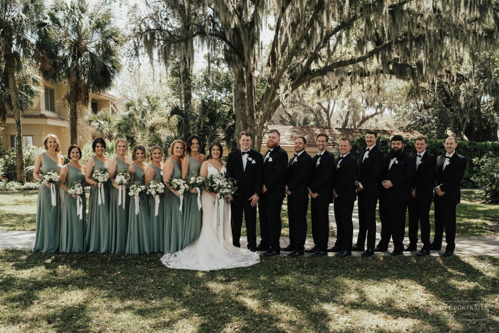 8 Bridesmaids in a line from left to center left where Bride, in white, is holding bouqet of flowers. Groom in black suit on right center. 8 groomsmen arrrayed to the right in matching suits.